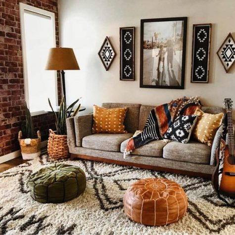 a boho living room with folksy artworks and pillows, leather and velvet ottomans, potted plants and a comfy sofa