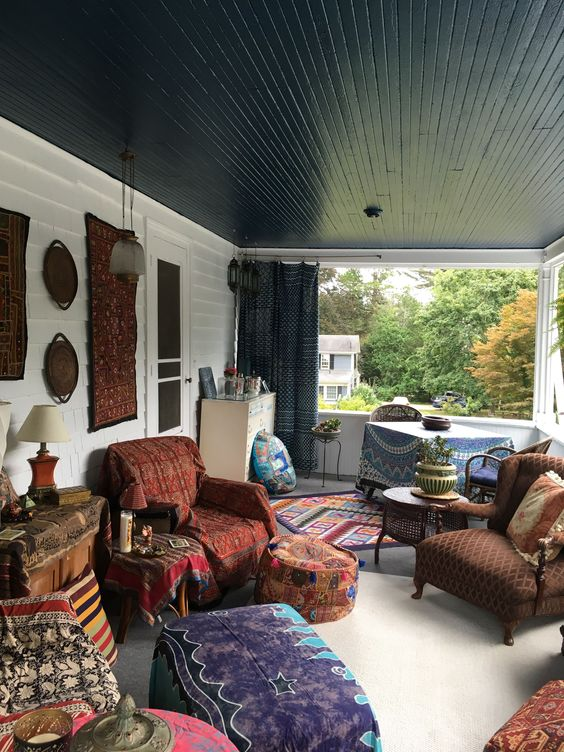 a boho meets retro porch with a dining and living room zone, decorative plates and rugs on the wall and lots of colorful ottomans