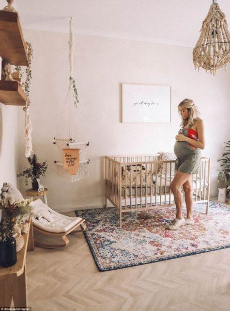 a boho nursery with a boho rug, a bead chandelier, a kids' rocker, hanging potted greenery