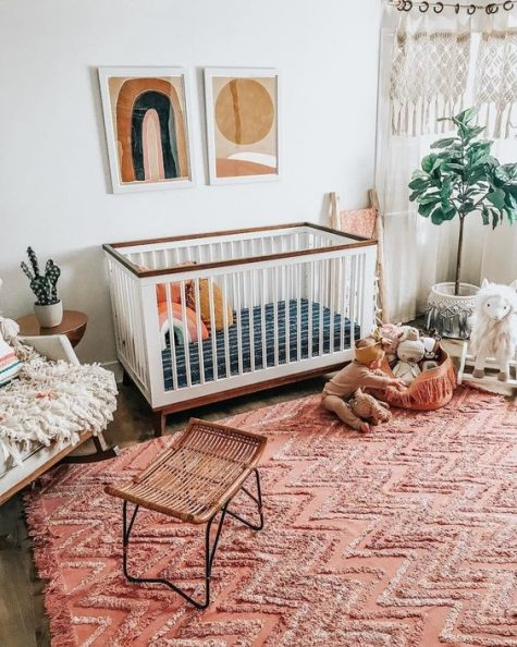 a boho nursery with a bright red rug, boho hangings, mid century modern artworks and fluffy touches