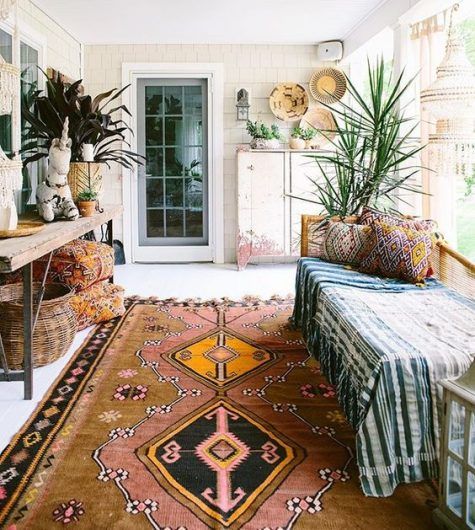 a boho porch done with a daybed, a wooden console, lots of potted plants, baskets and printed textiles
