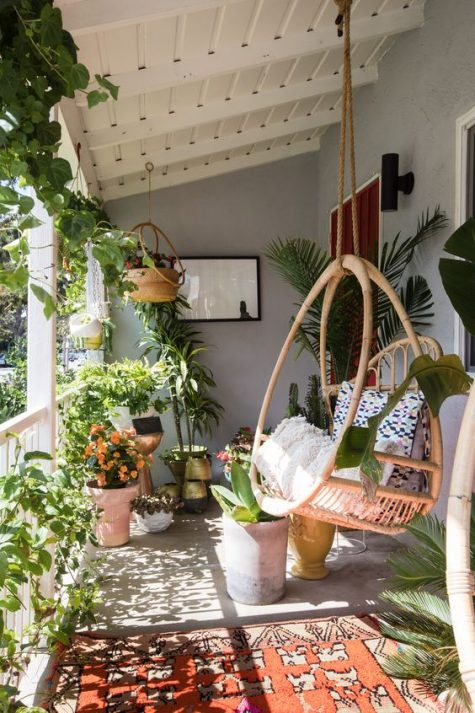 a boho porch turned into an orangery with lots of potted greenery and blooms and a large hanging rattan chair plus a rug
