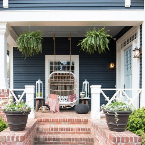 a boho porch with a large rattan loveseat, pillows, an ottoman, potted greenery and lanterns