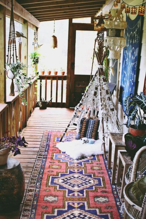 a boho porch with potted greenery hung here and there, a macrame teepee, a boho rug and lanterns