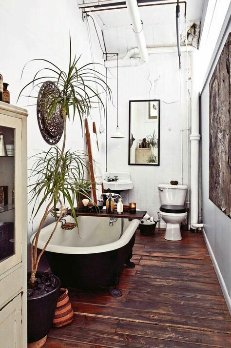 a boho rug on the wall, potted plants, a mirror, a rich stained wooden caddy with various bathroom stuff and candles