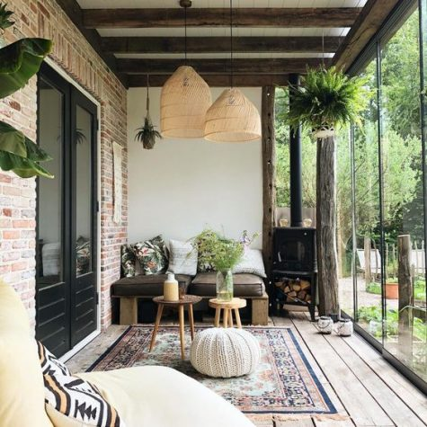 a boho screened porch with pallet furniture, pillows, wicker lamps, boho rugs and a crochet ottoman