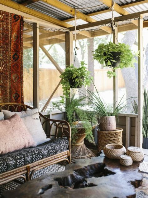 a boho screened porch with rattan furniture, a living edge table, potted greenery and boho textiles plus jute jars