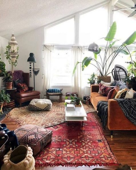 a boho space with a rust velvet sofa, boho rugs and ottomans, floor lamps and potted plants