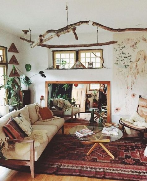 a boho space with boho rugs and pillows, branch hangings, a mirror, a glass coffee table and potted plants