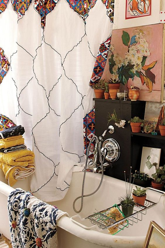 a bold boho bathroom with bright textiles - towels and a curtain, potted greenery and blooms all over