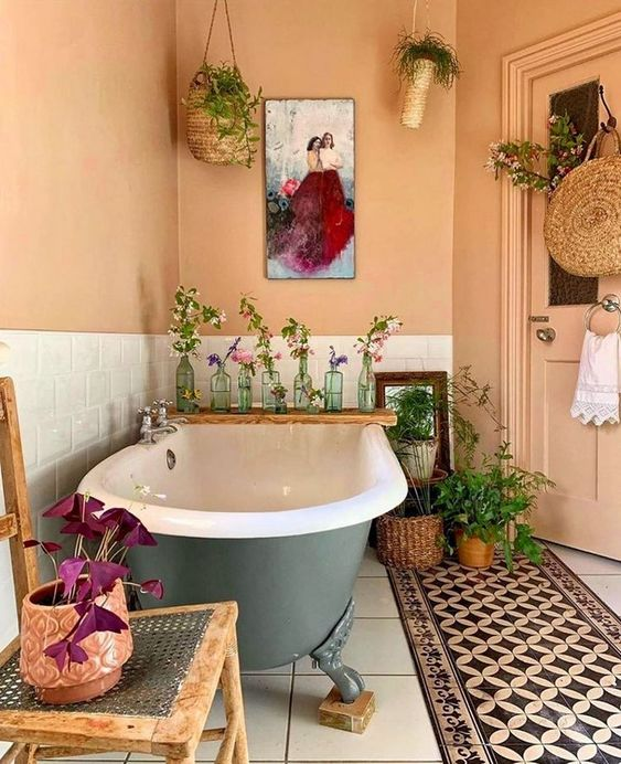 a bold boho meets vintage bathroom with buttermilk walls, a bold rug, a grey clawfoot tub, potted greenery and wicker touches