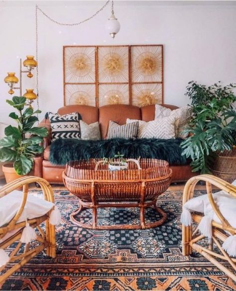 a bright Moroccan living room with a rust leather sofa, rattan chairs, potted plants and Moroccan lamps