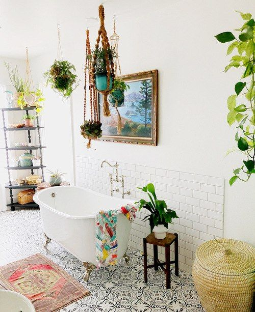 a bright bathroom with a gypsy feel - a bright boho rug, bold towels, potted greeneert and a wicker basket for storage