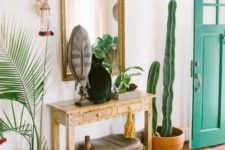 a bright boho entryway with a sleek wooden console, a catchy stool that matches, potted plants, a mirror in an arnate frame and some boho art