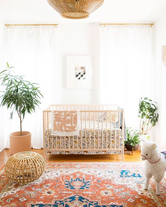a bright boho gender neutral nursery with bright bedding, a colorful rug, potted greenery and sheer curtains