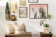 a bright boho hallway with a wooden bench, boho fringe pillows, a baket for storage and a gallery wall with artworks, hangings and potted plants