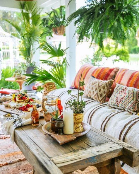 a bright boho porch with a comfy sofa, lanterns and potted plants plus a weathered wood table