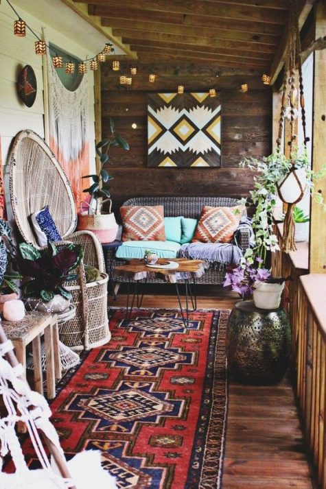 a bright boho porch with a wicker sofa and a peacock chair, a hairpin leg table, a geometric artwork, lights, boho textiles and lots of decor