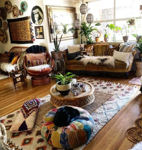 a bright boho space with colorful ottomans, pillows, a rattan chair, wicker lamps, a bold gallery wall and potted plants