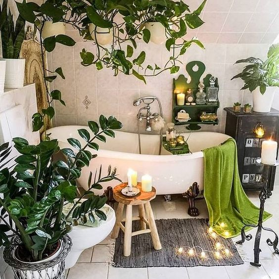 a calming boho bathroom with potted plants, green touches, a free-standing bathtub, candles and a rug on the floor