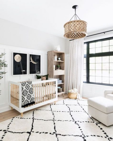 a catchy neutral nursery with touches of black for drama, prints, a wooden lamp and furniture