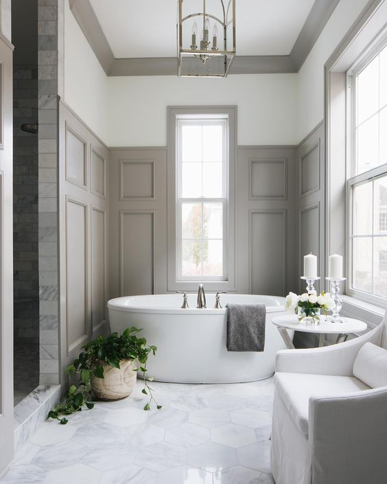 a chic bathroom with marble hex tiles, grey paneling on the walls and a minimalist oval tub