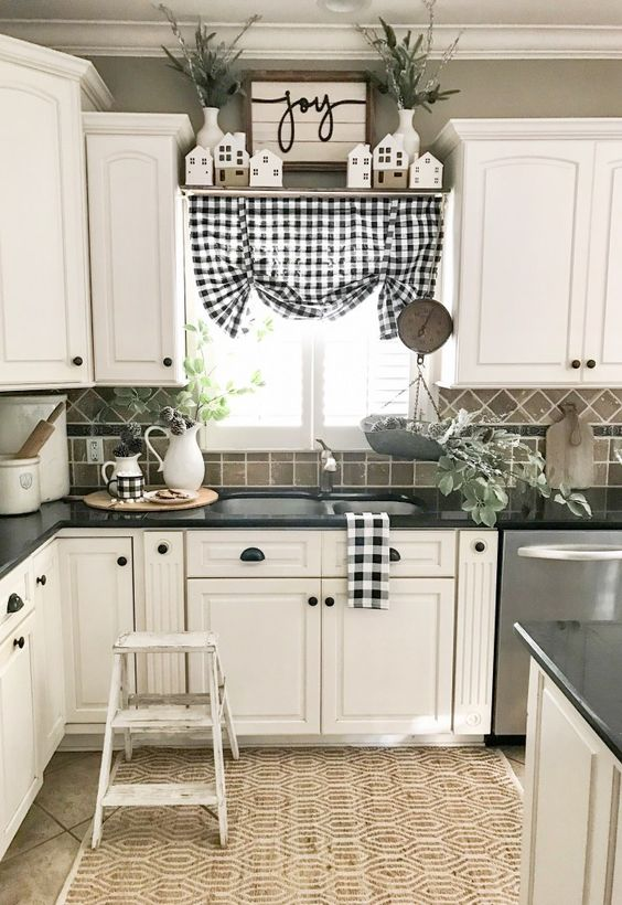 a chic farmhouse kitchen done in black, grey and white, plaid textiles, black handles and a jute rug