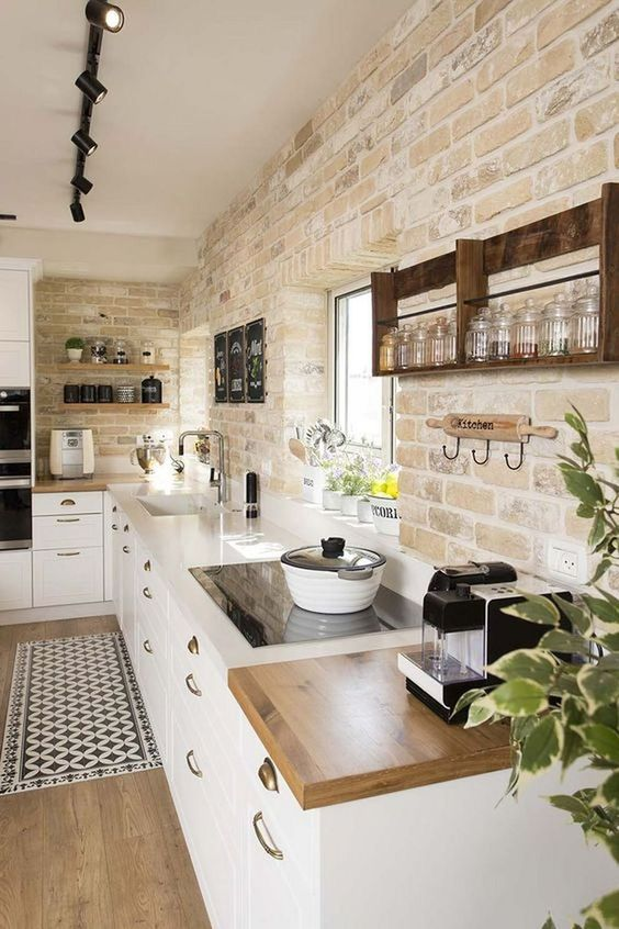 a chic farmhouse kitchen with a whitewashed brick backsplash, white cabinets, butcherblock countertops and a printed rug