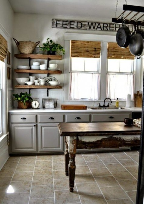 a chic farmhouse kitchen with vintage grey cabinets, floating wooden shelves, a shabby chic stained table as a kitchen island