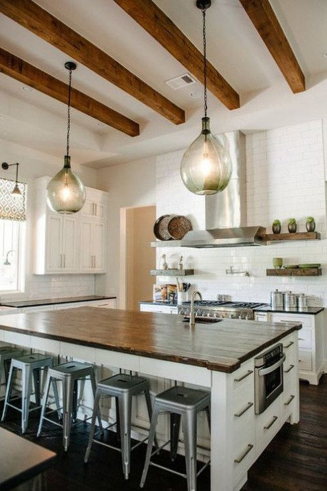 a chic farmhouse kitchen with wooden beams on the ceiling, large pendant lamps, dark butcherblock countertops and metal stools