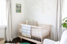 a chic gender neutral nursery in white, with a pretty mobile, a green ottoman, boho rugs and pompom curtains