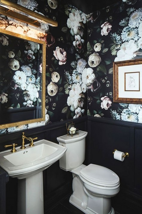 a chic powder room done with moody realistic floral wallpaper and black wainscoting