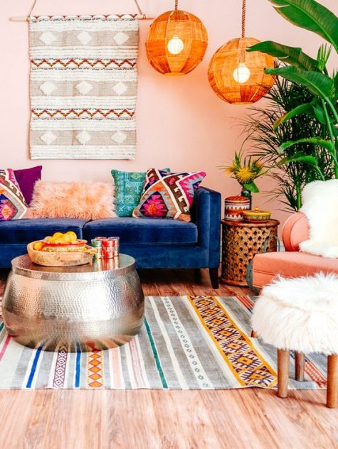 a colorful boho living room with bright lampshades, pink walls, boho rugs and pillows and a hammered metal coffee table