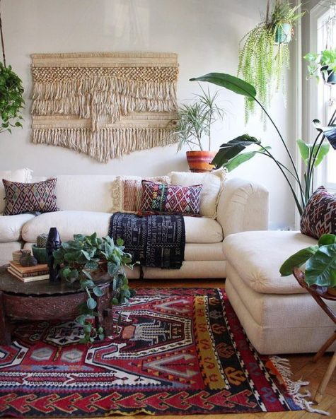 a colorful boho living space with a macrame hanging, a boho rug and pillows, potted greenery and neutral furniture