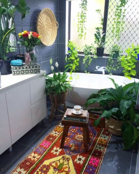 a colorful boho rug and lots of potted plants plus a basket on the wall make the bathroom free-spirited