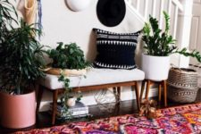 a colorful entryway with a white bench, a colorful boho rug, potted plants, a black printed pillow and baskets for storage