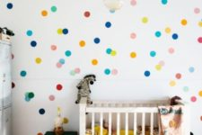 a colorful gender neutral nursery with colorful polka dots, bright bedding and green furniture