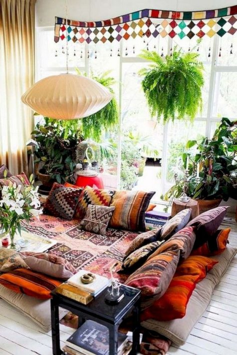 a colorful gypsy living room with a conversation zone, boho pillows and blankets, potted greenery and a lamp