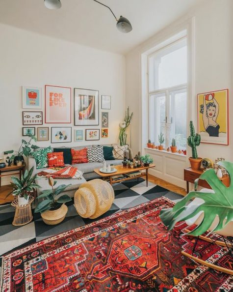 a colorful retro boho meets mid-century modern living room with folksy rugs and pillows, wicker touhes, potted cacti and succulents