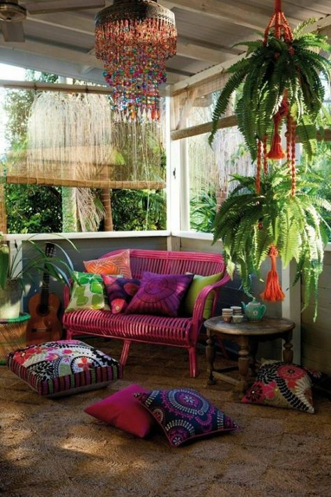 a colorful screened gypsy porch with potted greenery, a hot pink loveseat, a carved wooden table and colorful pillows
