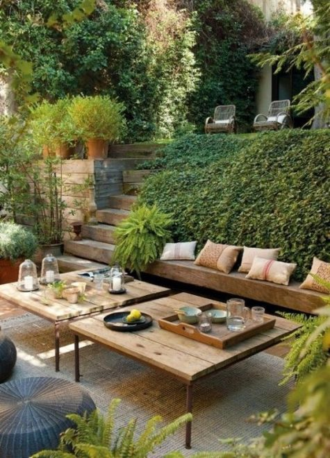 a contemporary meets rustic terrace with a built-in bench, wicker ottomans and low wooden tables