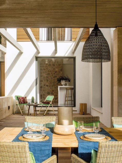 a contemporary rustic terrace with wicker furniture, a wooden table, a wicker lampshade and folding chairs