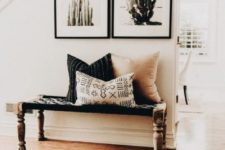 a cozy boho desert entryway with a luxurious rug, a woven bench, a couple of cacti artworks and boho pillows