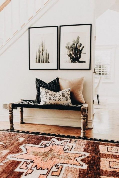 a cozy boho desert entryway with a luxurious rug, a woven bench, a couple of cacti artworks and boho pillows