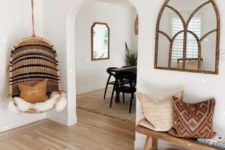 a cozy boho entry with a wooden bench, a leather bag for storage, boho pillows, a framed window-like mirror, a boho rug and a wicker hanging chair