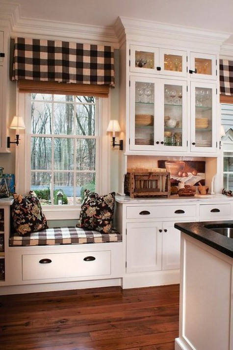 a cozy farmhouse kitchen with white cabinets and metal handles plus much plaid pattern incorporated