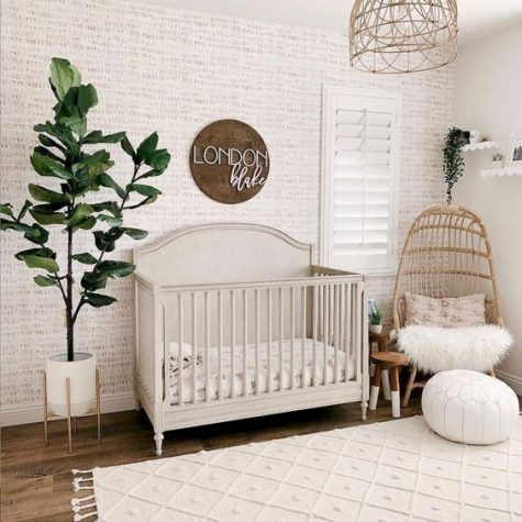 a cozy neutral modern nursery with wallpaper walls, a sign, wicker chairs and a lampshade, potted greenery