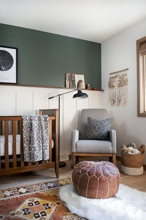 a cozy nursery with an accent wall in dark green and with white wainscoting to make the wall stand out even more