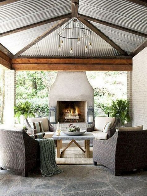 a cozy rustic patio with a large fireplace, wicker chairs and a bulb chandelier make up a cool outdoor living room