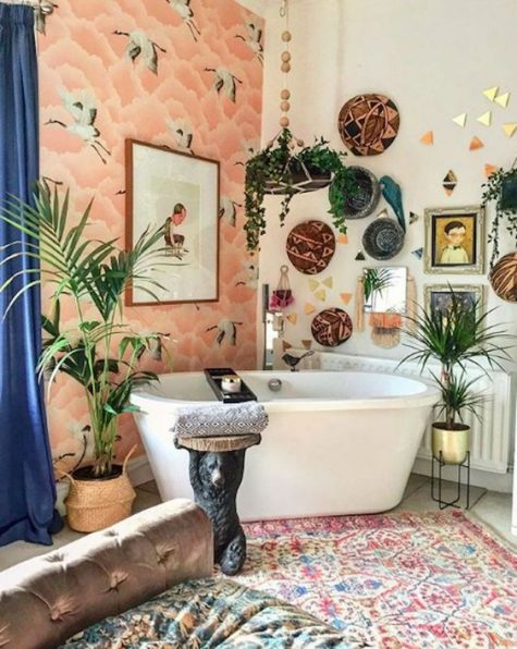 a crazy boho bathroom with a bright wallpaper wall, decorative baskets, potted plants, a gallery wall, boho rugs and textiles